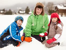 children building snowman outdoors