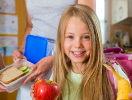 girl holding school lunch snack