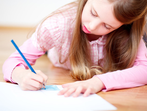 Girl coloring with blue pencil