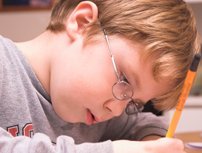 Boy writing with pencil