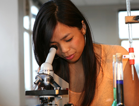 Teen girl looking through microscope