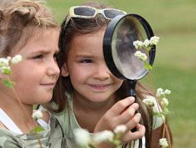 Two girls looking through magnifying glass