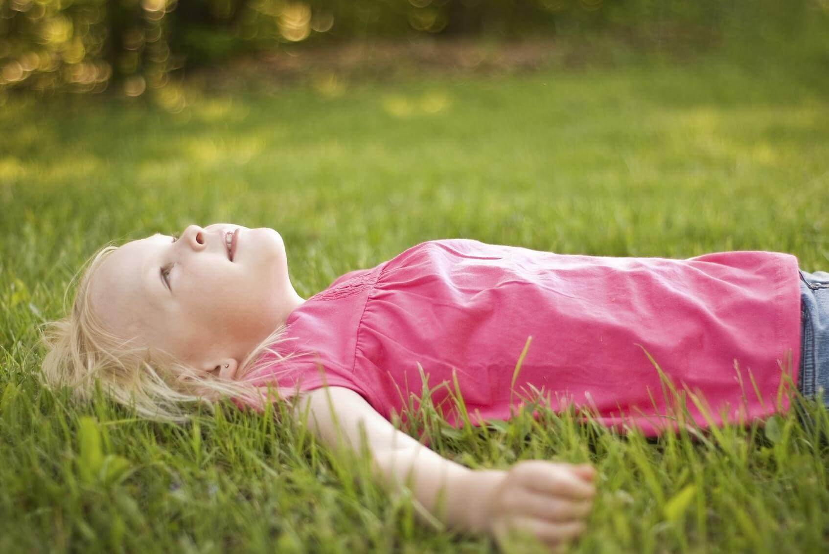 Little Girl Laying in Green Grass