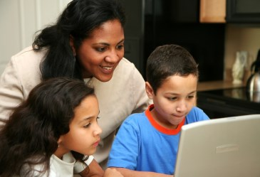Mom and kids playing on laptop computer