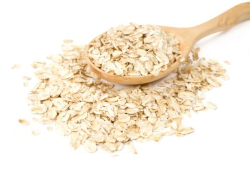 Spoonful of oats on white background