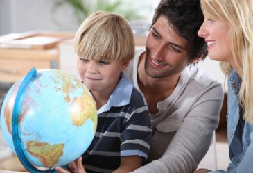 Parents in classroom with young child looking at globe