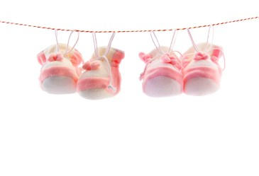 Pink booties on clothesline against white background
