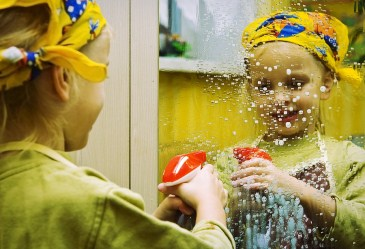 Little girl cleaning mirror