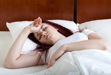 Woman in bed sick to her stomach