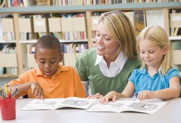 Young students reading with teacher