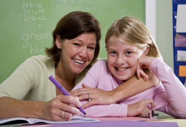 Smiling teacher and student in classroom