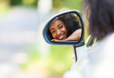 Teen driver looking in car side mirror