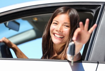 Smiling teen girl holding car keys out window
