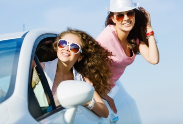 Two teen girls hanging out of car windows