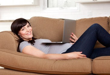 Pregnant woman laying on couch watching movie on computer