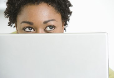 Woman looking over computer monitor