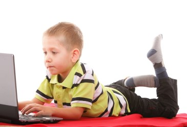 Young boy laying on stomach playing with computer