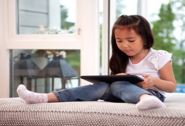 Young girl sitting on couch playing with tablet computer