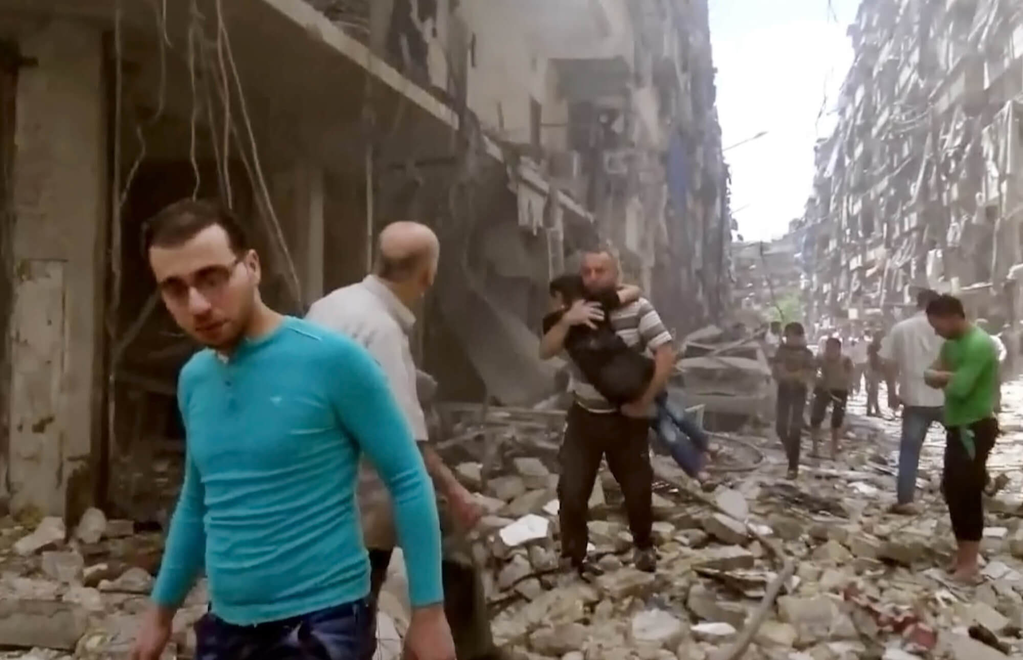 surviors walk through rubble and debris from airstrike in Syria