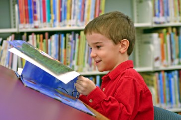 Starting kindergarten, boy reading in library to prepare for school