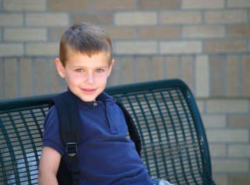 Starting kindergarten, boy waiting for school bus for first time