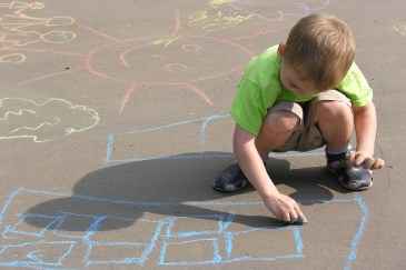 child drawing with sidewalk chalk