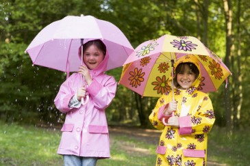 Summer camp essentials, two girls in raincoats with umbrellas