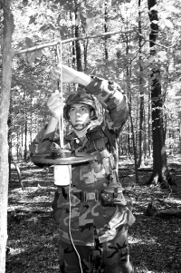 Army Spc. Clark Dutterer, a preventive medicine specialist at the U.S. Army Center for Health Promotion and Preventive Medicine at Aberdeen Proving Ground, Maryland, sets a light trap to catch adult mosquitoes in the Maryland woods. The mosquitoes are then tested to see if they are carrying certain diseases. The trap was supplied by the Centers for Disease Control and Prevention.
