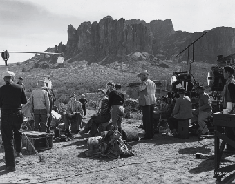Behind the camera on location in the Arizona desert filming Universal's comedy Lady in a Jam (1942) is seen Irene Dunne (sitting, center) dressed for a scene in the film.