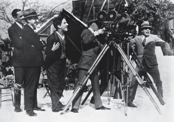 Chaplin on location shooting The Gold Rush while in tramp regalia.