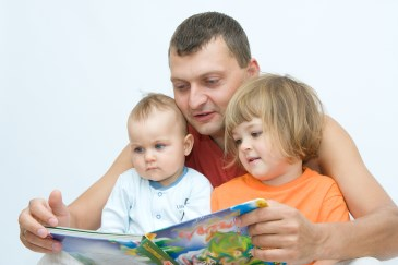 father reading to baby and toddler