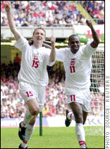 Emmanuel Olisadebe (right) celebrates a goal for Poland