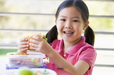 Starting kindergarten, girl eating school lunch as practice for first day of school