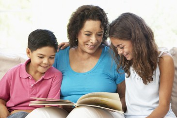 grandparent, grandchildren reading a book