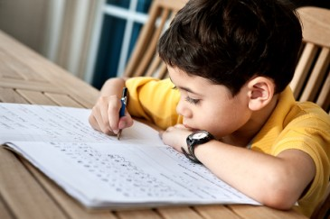 Starting kindergarten, young boy doing homework for kindergarten