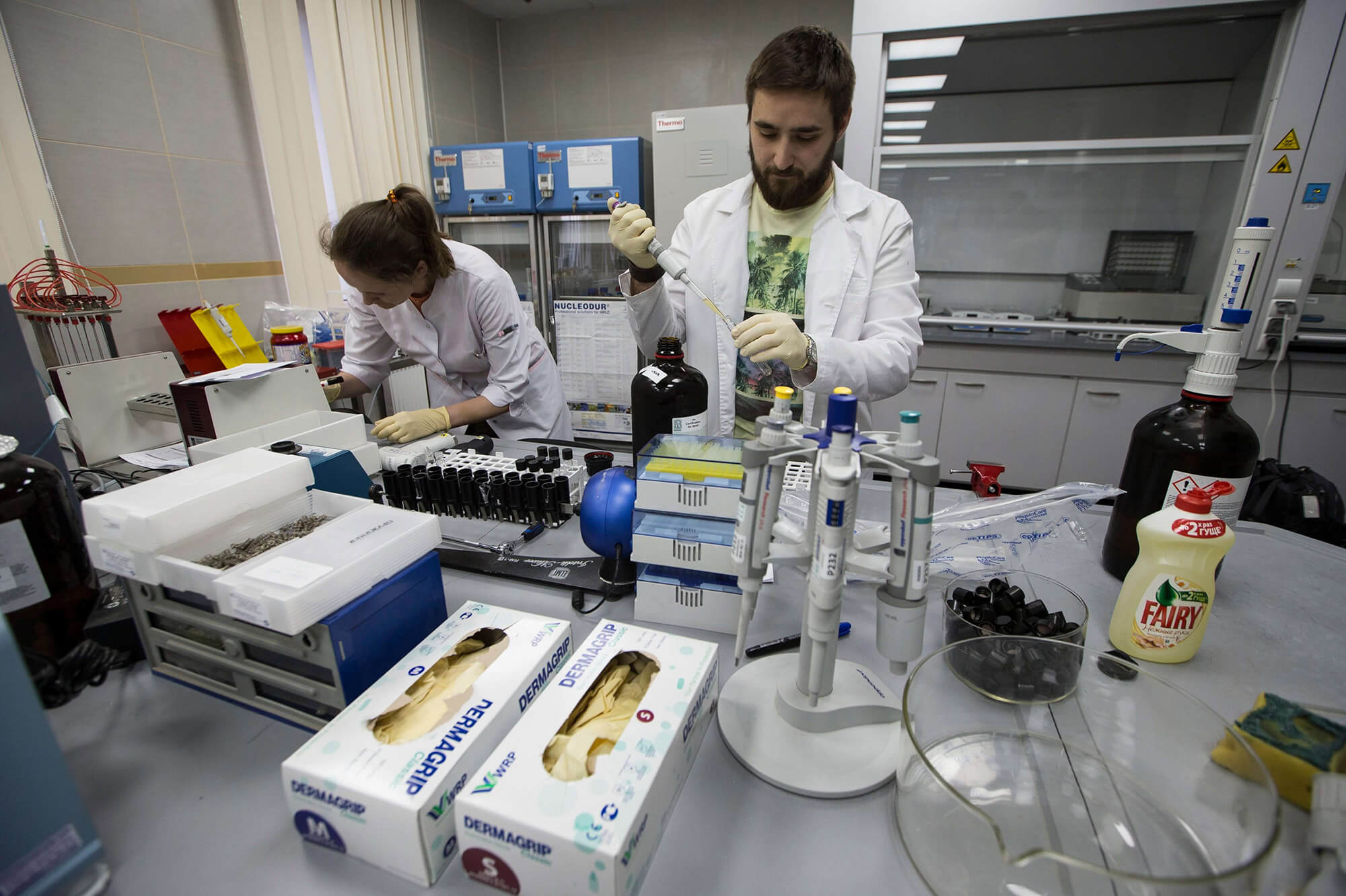 Image of two scientists in white coats in laboratory.