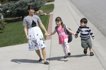 Starting kindergarten, mother and two kids walk to school or preschool