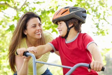 mother helping son ride bike
