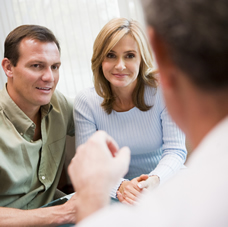 mature couple discussing fertility with doctor