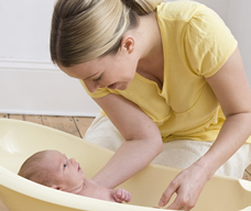 woman bathing newborn baby