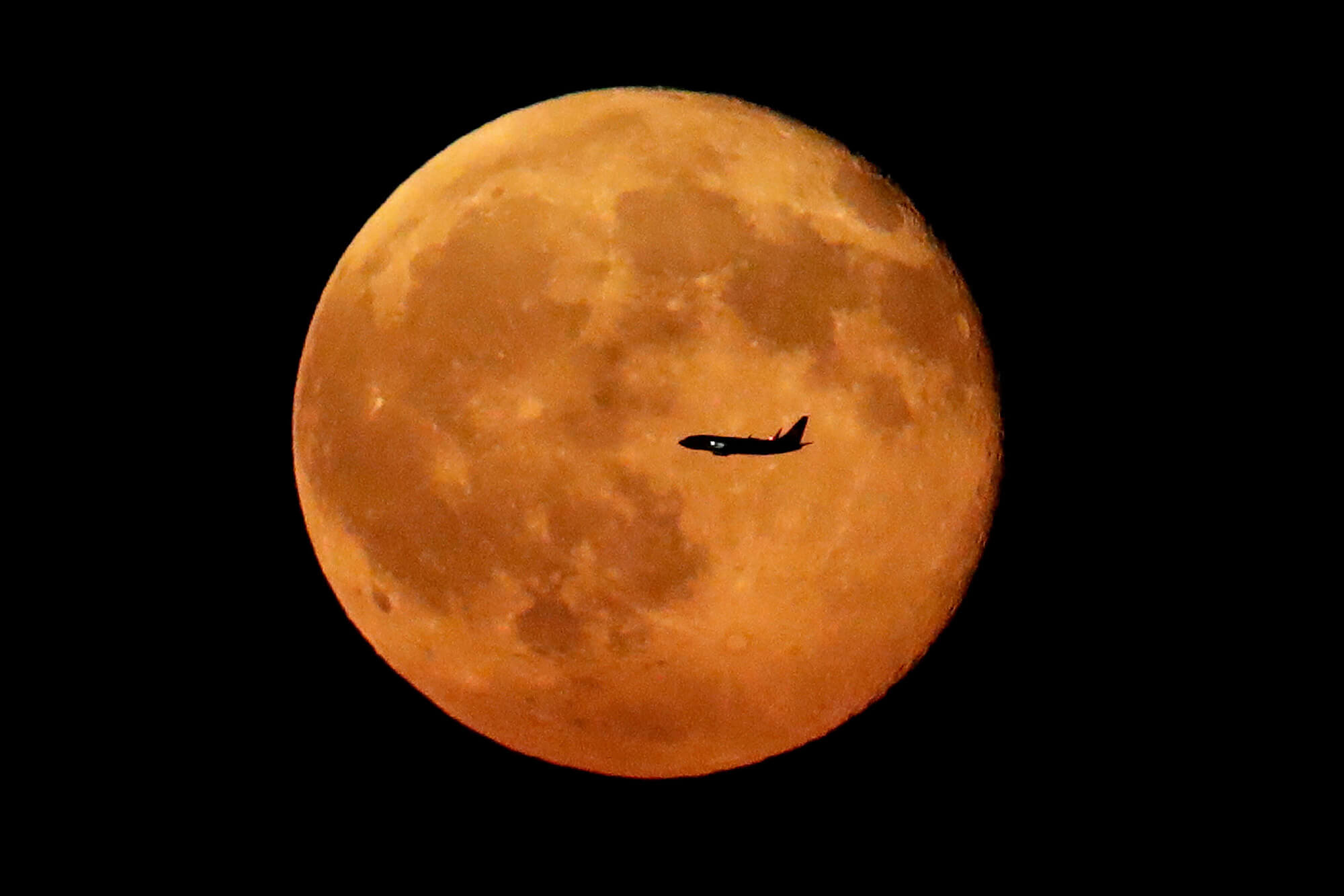 Image of the moon with plane in front of it.